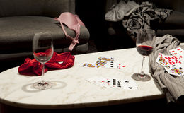Losing At Strip Poker. The outcome of a game of strip poker with women's clothing strewn over a chair and table and a man's shirt on the right side.Two partly Royalty Free Stock Photo