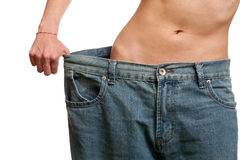 Before and after losing weight. Young woman wearing her old jeans, showing her body after losing weight Stock Photo