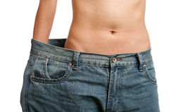 Before and after losing weight. Young woman wearing her old jeans, showing her body after losing weight Stock Photography
