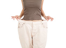 Losing weight. Anonymous woman showing how much weight she lost, white background Royalty Free Stock Photo