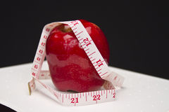 Losing Weight - Apple. Red bright apple with tape measure wrapped around it for concept of eating healthy and losing weight Royalty Free Stock Image