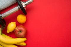 Losing weight concept on red background. Losing weight concept with dumbbell, towel, lemon, tangerine, and apple on red background Royalty Free Stock Images