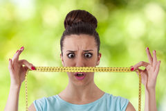 Losing weight. Expression girl with tape measure concept of losing weight Royalty Free Stock Image