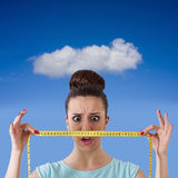 Losing weight. Expression girl with tape measure concept of losing weight Stock Image