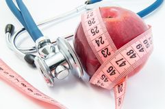 Losing weight with healthy food fruits and vegetables under doctor supervision. Red apple wrapped up by measuring tape and steth. Oscope, which exam of apple Stock Image