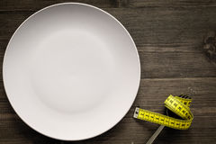 Losing weight. Strict diet. Empty plate and measuring tape on fork instead food on wooden background top view mockup Royalty Free Stock Photos