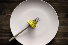 Losing weight. Strict diet. Empty plate and measuring tape on fork instead food on wooden background top view mockup Stock Image