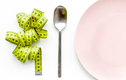 Losing weight. Strict diet. Empty plate and measuring tape on white background top view mockup Royalty Free Stock Photography