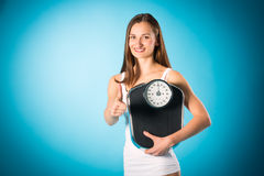 Losing weight - Young woman with measuring scale Royalty Free Stock Images