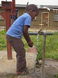 LOSOTHO TAP. A young African boy fills a plastic bag with water from an outdoor tap near his home in Maseru, Lesotho Royalty Free Stock Photos