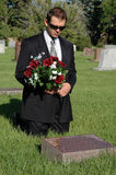 Loss. A man with a bouquet of flowers kneeling before a grave Royalty Free Stock Photos