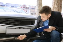 Loss adjuster inspecting car after  accident Royalty Free Stock Photography