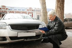 Loss adjuster inspecting car after  accident Royalty Free Stock Photo