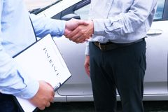 Loss Adjuster Insurance Agent handshake with Inspecting Damaged. Car Stock Image