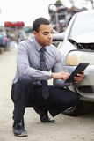 Loss Adjuster Using Digital Tablet In Car Wreck Inspection Stock Image
