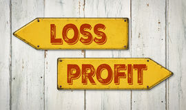 Loss or Profit. Direction signs on a wooden wall - Loss or Profit Royalty Free Stock Photo
