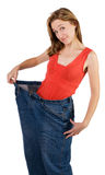 Loss of weight. Beautiful girl shows how she lost weight, isolated on white Stock Photos