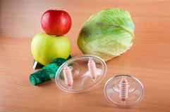 Loss weight concept. Red, green apple, measuring tape, cabbage, massagers on wooden table Royalty Free Stock Images
