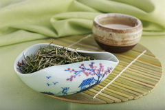 Lossa gröna teblad och koppen av grönt te Arkivbild