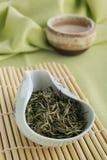 Lossa gröna teblad och koppen av grönt te Fotografering för Bildbyråer