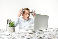 Upset child is feeling frustration. Losses in business concept. Frustrated little boy is expressing disappointment while sitting at table with money in his hands Royalty Free Stock Photos
