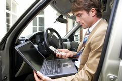 Lost. Businessman on a business trip is sitting in his car with his notebook Royalty Free Stock Photo