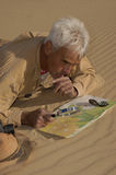 Lost 2. Adventurous senior man lost in the desert thinking out his plan Stock Image