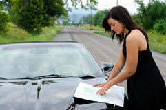 Lost. Beautiful Fashionable Young Woman Looking At A Map On The Hood Of Her Sports Car Royalty Free Stock Photo
