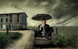 Lost. Businessman sitting on armchair with umbrella in the countryside Royalty Free Stock Images