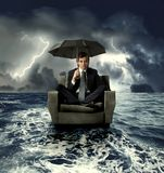 Lost. Businessman on an armchair lost in the sea Royalty Free Stock Photo