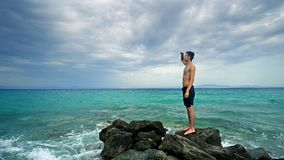 Lost alone male teen standing on sea rock. And navigating horizon Stock Photos