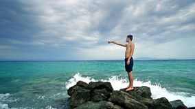 Lost alone male teen standing on sea rock. And navigating horizon Stock Photo