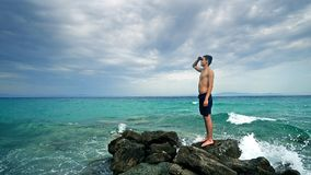 Lost alone male teen standing on sea rock. And navigating horizon Stock Images