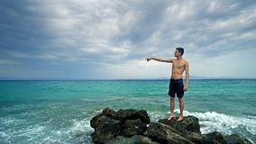 Male teen standing on sea rock and navigating horizon. Lost alone male teen standing on sea rock and navigating horizon Stock Photography