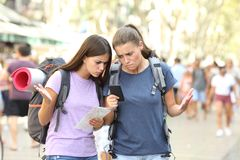 Lost backpackers confused with gps location. Two lost backpackers confused with gps location using a smart phone in the street royalty free stock image