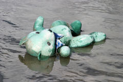 Lost bear 1. A blue teddy bear lays in a creek of water lost and lonely waiting to be found by its owner stock image