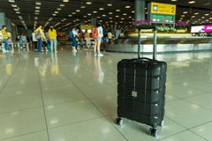 Lost black hardshell carry-on roller luggage left unattended at the baggage reclaim area at airport stock image