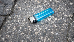 Lost blue cigarette lighter at the asphalt Royalty Free Stock Photography