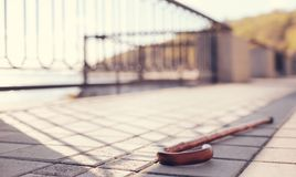 Wooden cane lying on paved sidewalk. Lost on bridge. The focus being on a wooden cane lying on a paved sidewalk of a bridge, having been lost by its owner royalty free stock photos