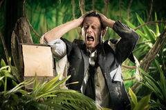 Lost in business jungle. Desperate businessman lost in jungle with head in hands and empty sign Stock Images