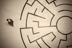 Lost business man looking for a way in circular labyrinth Royalty Free Stock Photo