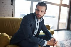 Lost in business thoughts...Thoughtful handsome young businessman is thinking about business while sitting on the sofa. In his modern office. Fashion look royalty free stock images