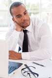 Lost in business thoughts. Thoughtful young African man in shirt and tie leaning his head on hand and looking away while sitting at his working place Royalty Free Stock Photos