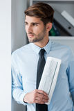 Lost in business thoughts. Thoughtful young man in shirt and tie holding newspaper and looking through a window while standing in office Royalty Free Stock Images