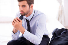 Lost in business thoughts. Thoughtful young man in shirt and tie touching his chin with mobile phone and looking away while sitting on the bed Royalty Free Stock Photo
