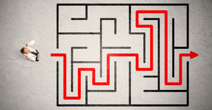 Lost businessman found the way in maze with red arrow Stock Images