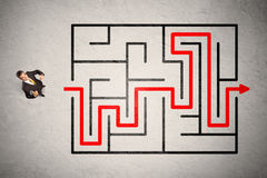 Lost businessman found the way in maze with red arrow Stock Photo