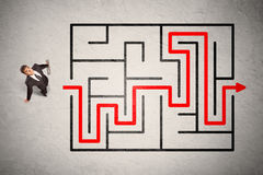 Lost businessman found the way in maze with red arrow Stock Photos
