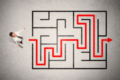 Lost businessman found the way in maze with red arrow Royalty Free Stock Photography