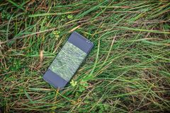 A lost cellphone in the high grass. The cellphone artist is a Samsung s8, with edge screen, but with no indicators of the exact phone royalty free stock photos